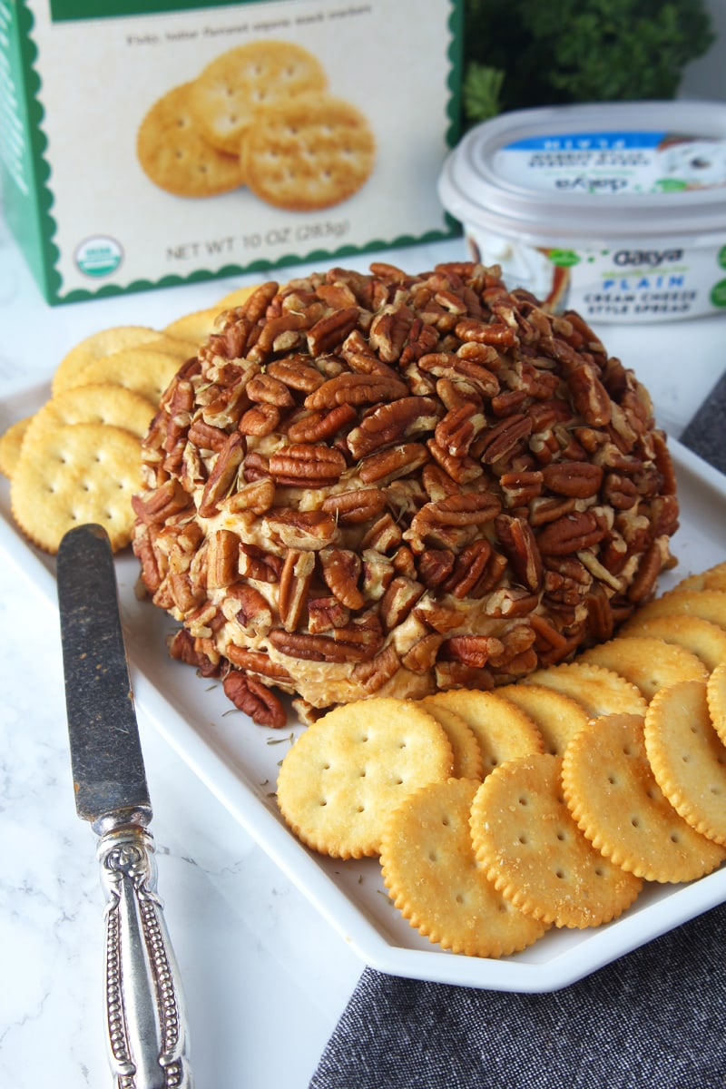 When the holiday parties strike, try this easy vegan cheese ball! Combining smoky flavor with delicious cheddar cheese + rolled in pecans and herbs, you're sure to wow both vegans and non-vegans. Takes only 10 min to make, and is naturally dairy-free and gluten-free. Just make sure to buy an extra box of crackers! #vegancheeseballrecipes #vegancheeseballeasy #glutenfreevegancheeseball #veganappetizers #veganappetizerspartyeasy #veganchristmasappetizers #bohemianvegankitchen