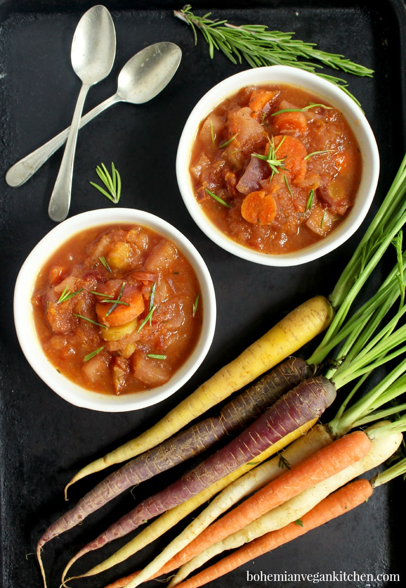 two bowls of carrot apple soup with fresh carrot bunch