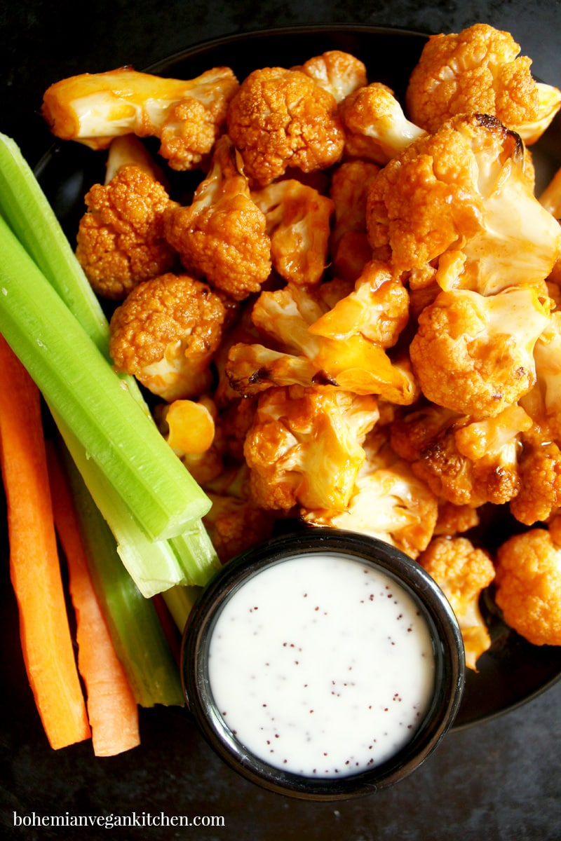 Spice up your party with these KILLER vegan buffalo cauliflower wings! Easy to pull together, you only need 10 minutes to assemble- let the oven do the rest! Serve with carrot and celery sticks, plus vegan ranch dressing to cool your taste buds. #veganbuffalocauliflower #veganbuffalocauliflowerwings #veganbuffalocauliflowerrecipes #veganbuffalocauliflowerglutenfree #bohemianvegankitchen