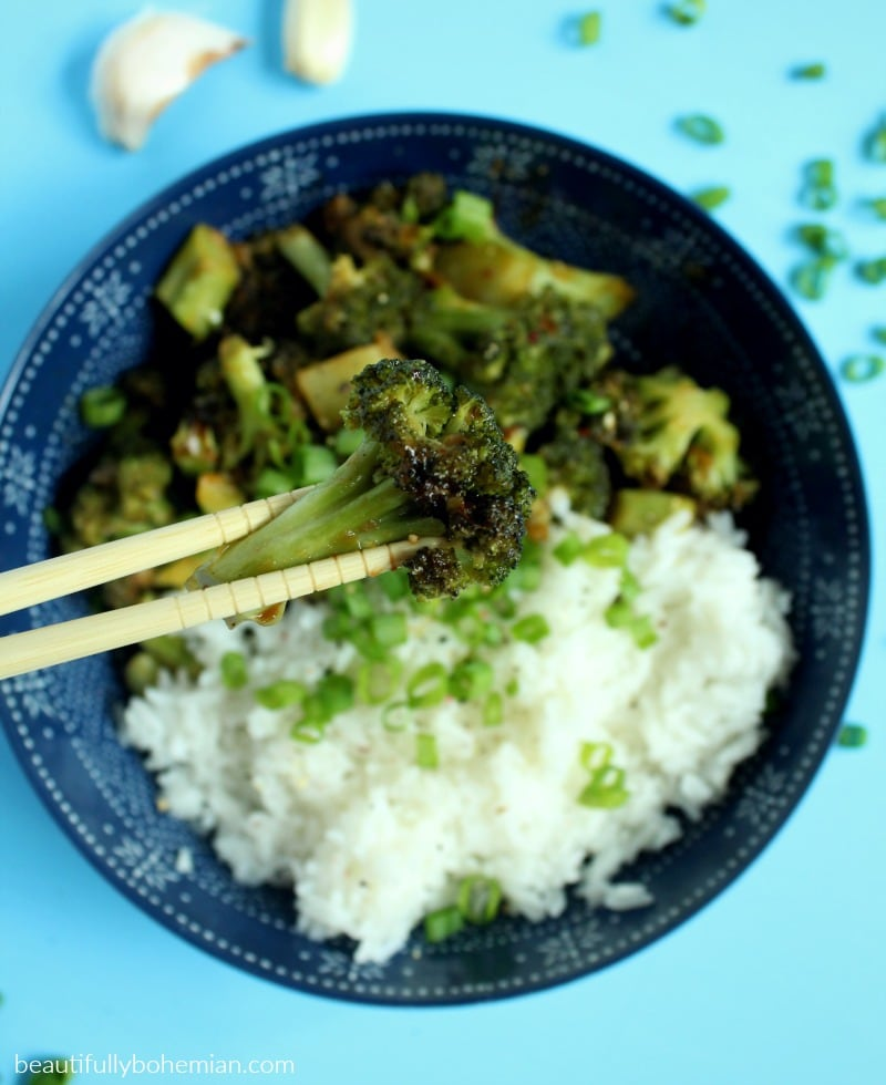 picture of broccoli being held by chopsticks