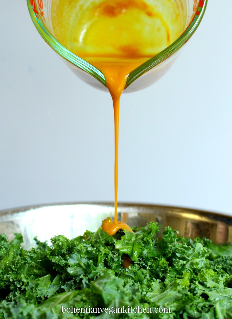 drizzle shot of dressing being poured on kale salad