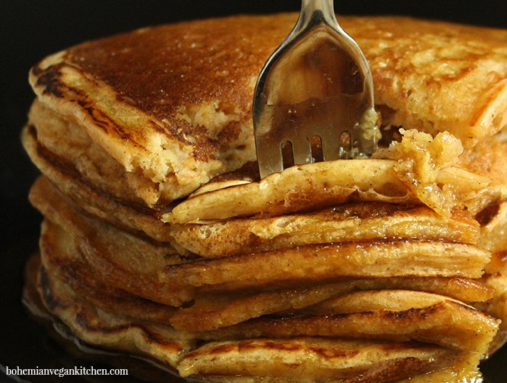Picture of a fork cutting into vegan pumpkin pancakes