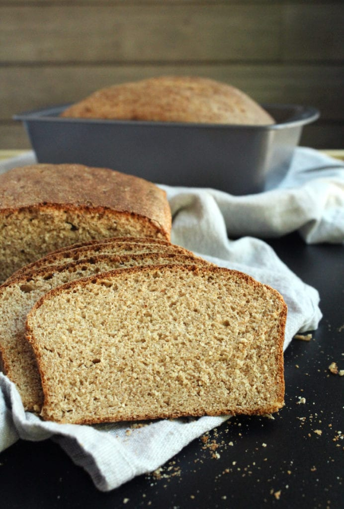 picture of homemade vegan bread freshly sliced with load tin in background.