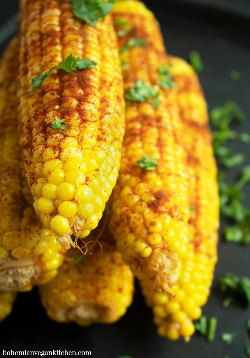 Need a summertime side dish that's vegan, allergy-friendly, and doesn't use imitation animal products? Try this healthy version of street corn, which takes only 5 minutes prep time and can be ready to eat in 30 minutes! #veganstreetcorn #dairyfreestreetcorn #bakedcornonthecoboven #bakedcornonthecob #vegansidedisheasy #bohemianvegankitchen