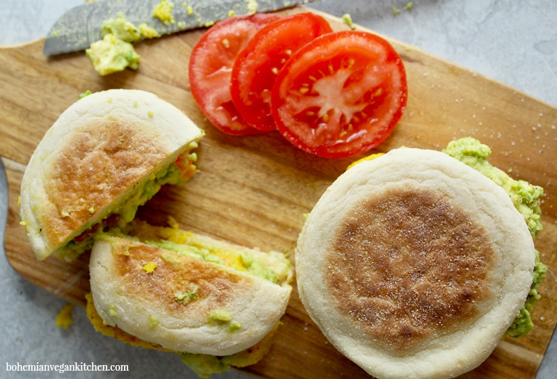 For a delicious (yet simple) breakfast, enjoy these vegan egg sandwiches, which are topped with juicy tomato sliced and smashed avocado! Completely vegan and soy-free, these breakfast sandwiches can be made gluten-free by using GF english muffins. #veganeggsandwich #veganeggsandwichbreakfast #veganeggrecipes #veganeggbreakfastsandwich #veganegg #bohemianvegankitchen