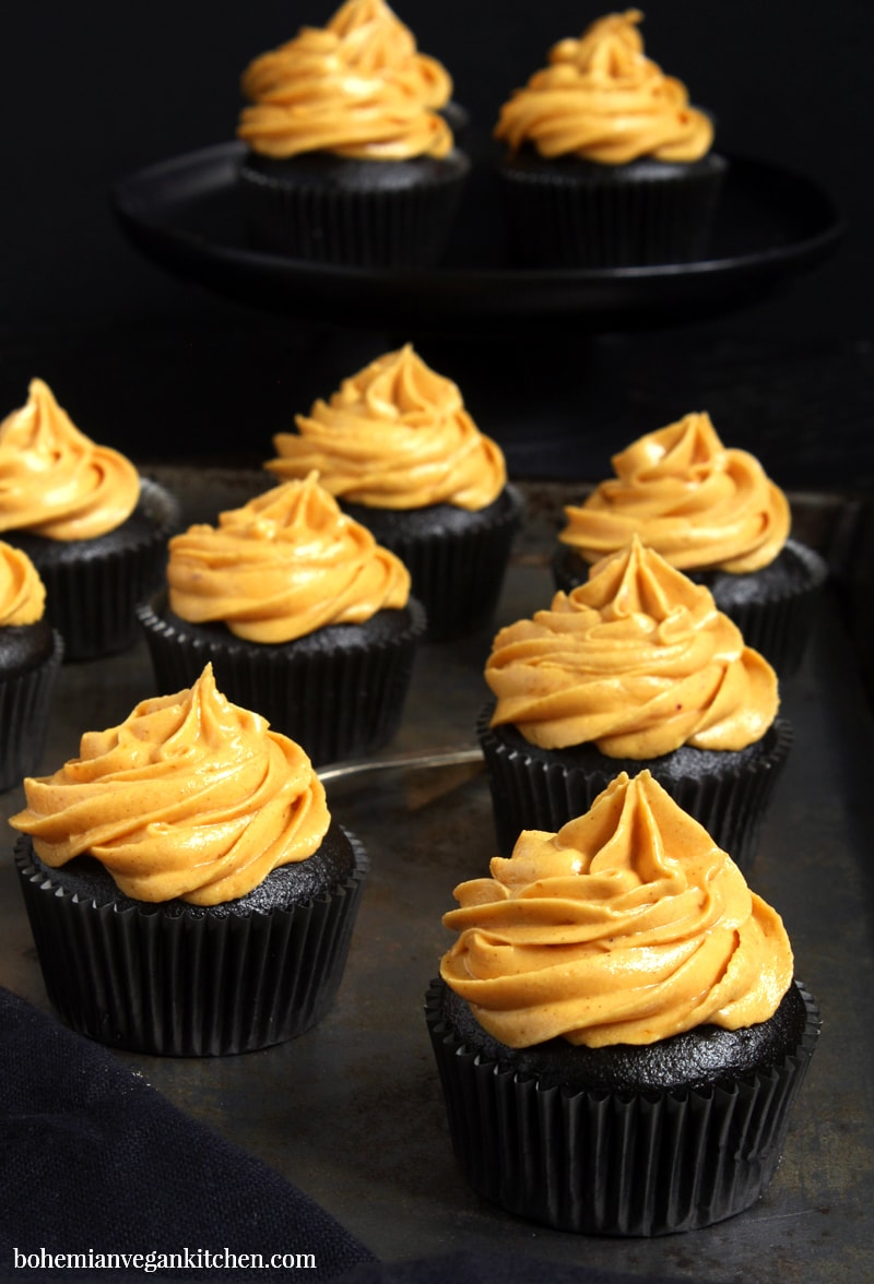 Make Halloween wicked delicious with these black chocolate coffee flavored cupcakes, topped with vibrant pumpkin pie frosting. These vegan Halloween cupcakes are easy to make, but result in a stunning finish that will put a spell on anyone who tastes them! #veganhalloweencupcakes #veganhalloweenrecipes #veganhalloweentreats #blackdesserts #veganhalloweendesserts #veganhalloweenfood #bohemianvegankitchen