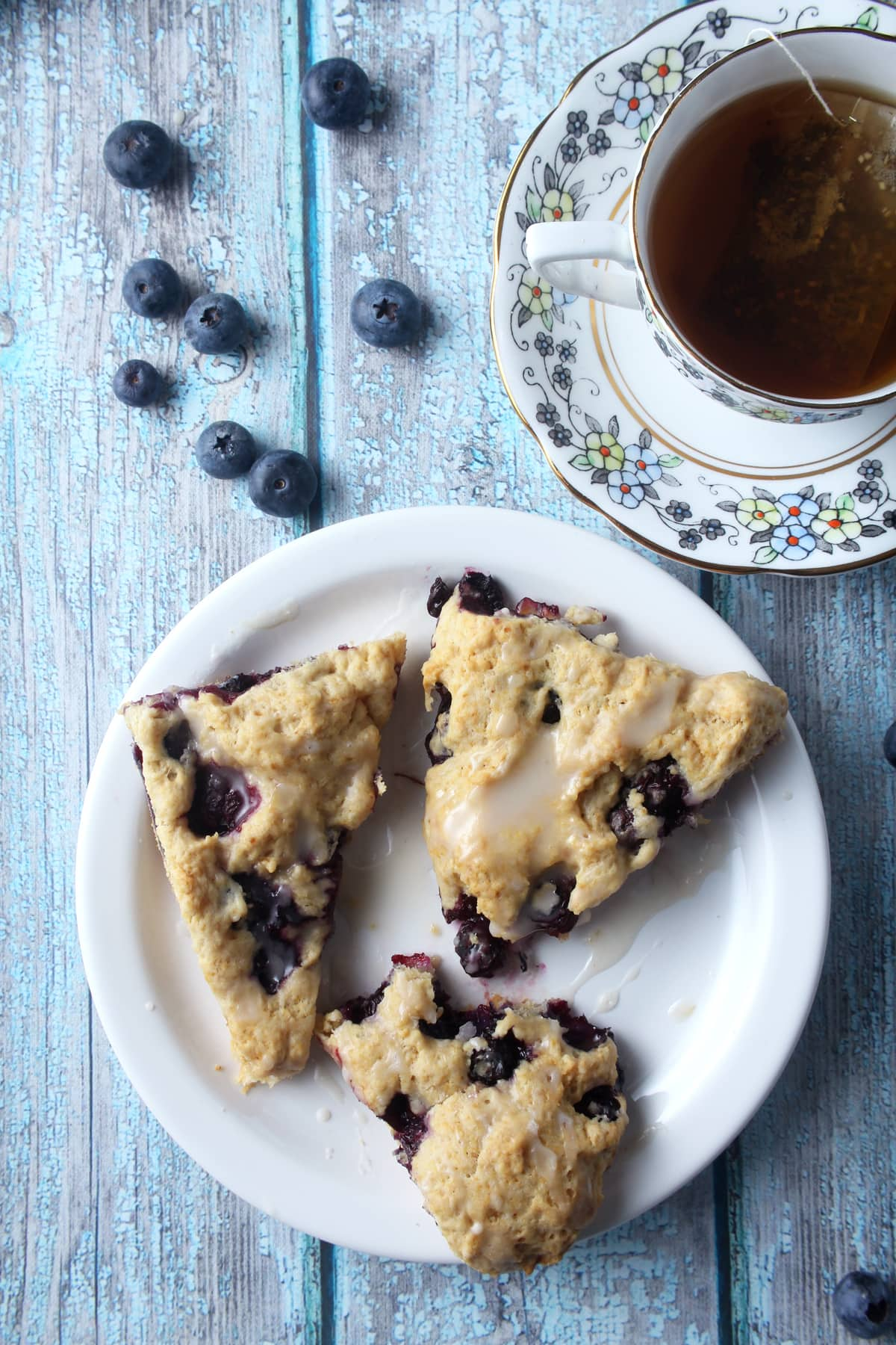 3 vegan blueberry scones on a plate, ready to eat