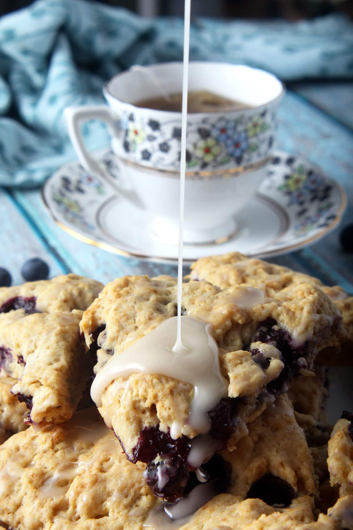 delicious glaze being drizzled on top of vegan blueberry scones