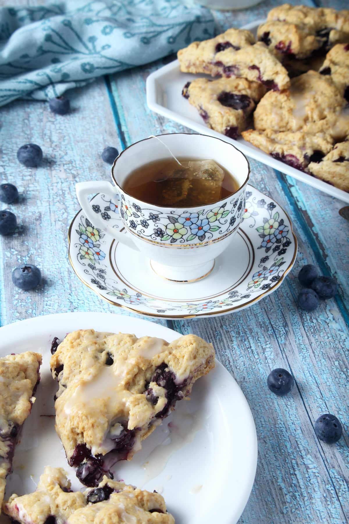 cup of tea with vegan blueberry scones in background