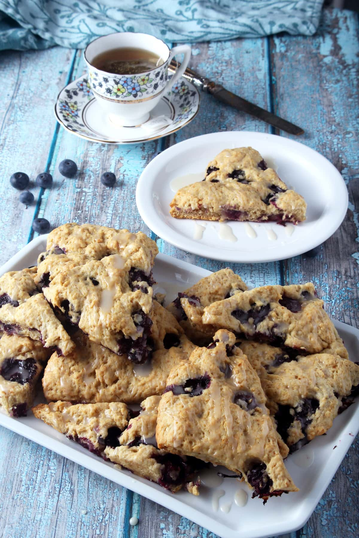 vegan blueberry scones with a piece on a plate in background