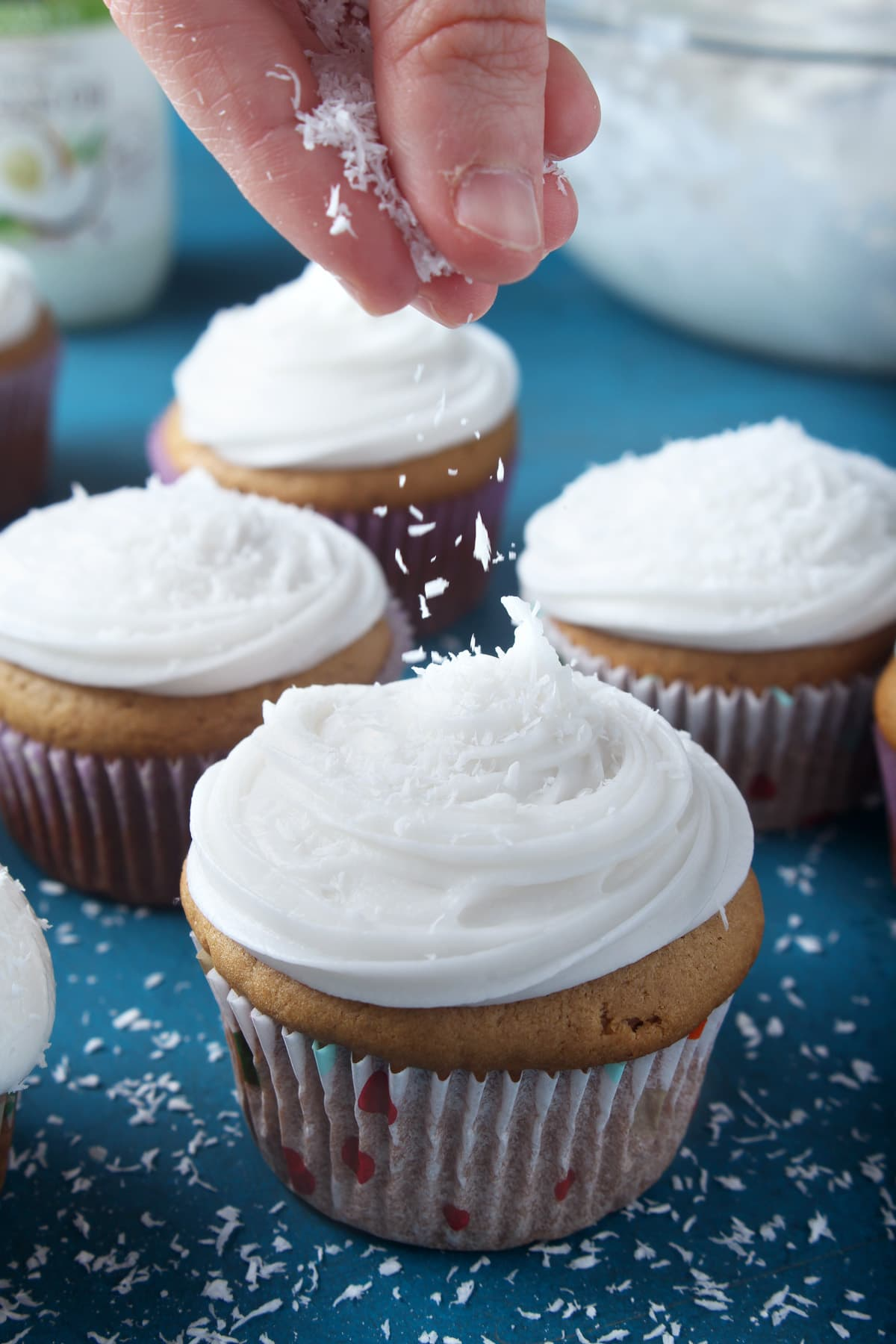 picture of coconut shavings being sprinkled on top of a cupcake