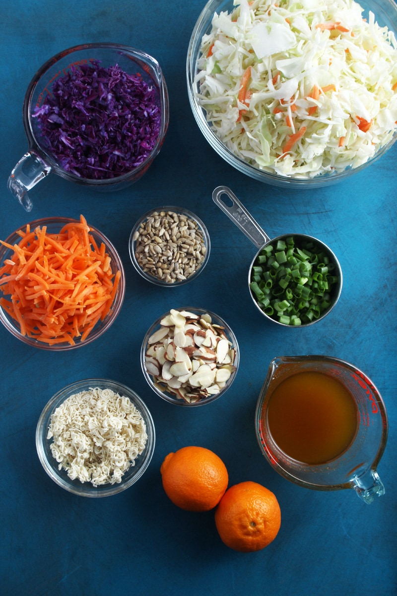 overhead shot of ramen noodle salad ingredients: red cabbage, green cabbage, carrots, sunflower seeds, green onions, almonds, ramen noodle bits, oranges, and dressing.