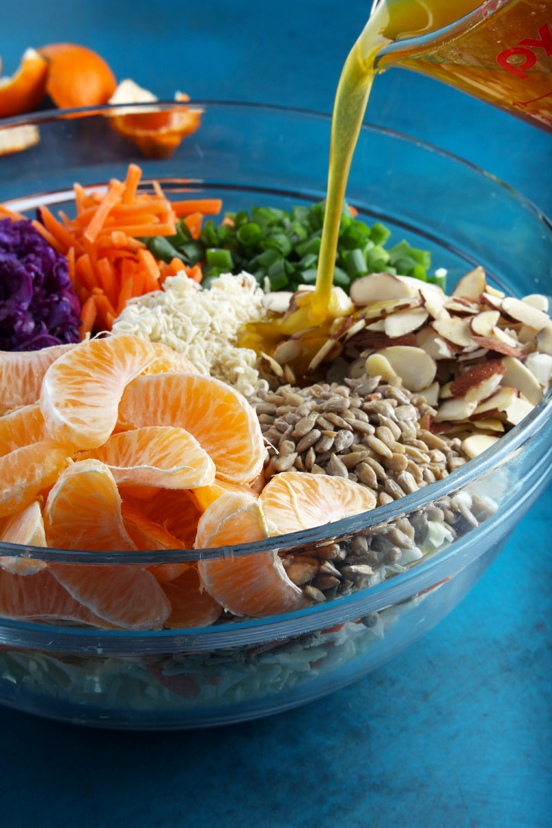 All the ingredients of ramen noodle salad with dressing poured on top.