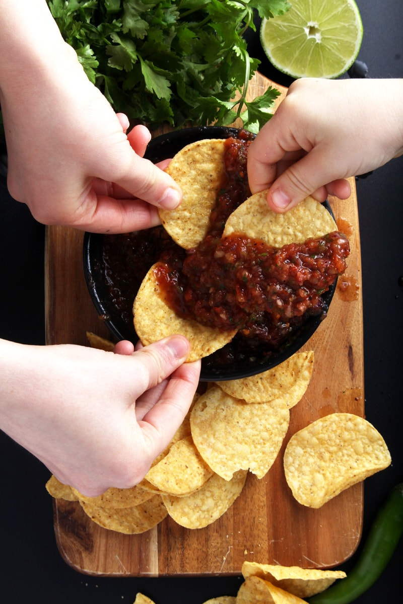 Picture of three kids hands dipping chips in salsa.