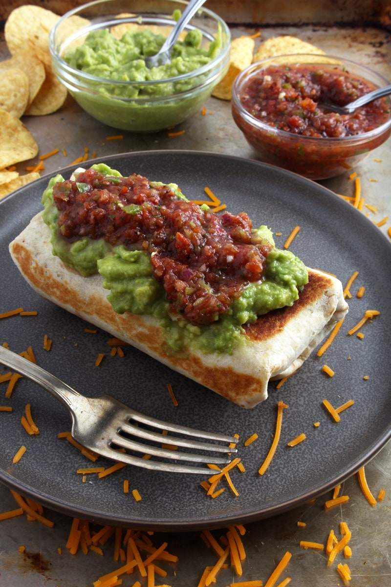 picture of single chimichanga with salsa and guacamole on top.