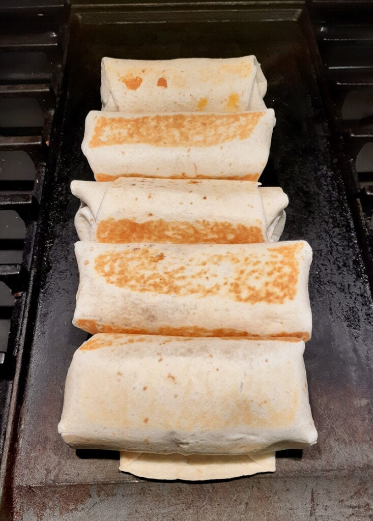 A picture of chimichangas being cooked on a griddle.
