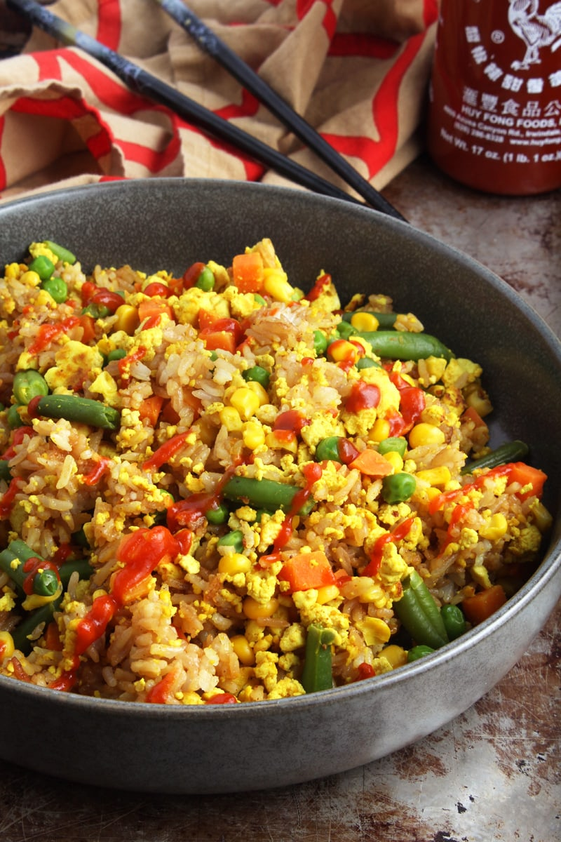 Close up picture of vegan fried rice with Sriracha sauce.
