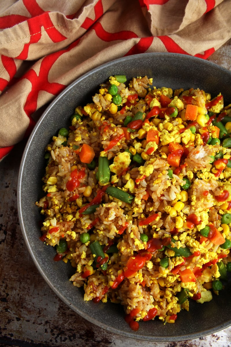 Picture (above shot) of vegan fried rice with vegetables and Sriracha sauce.