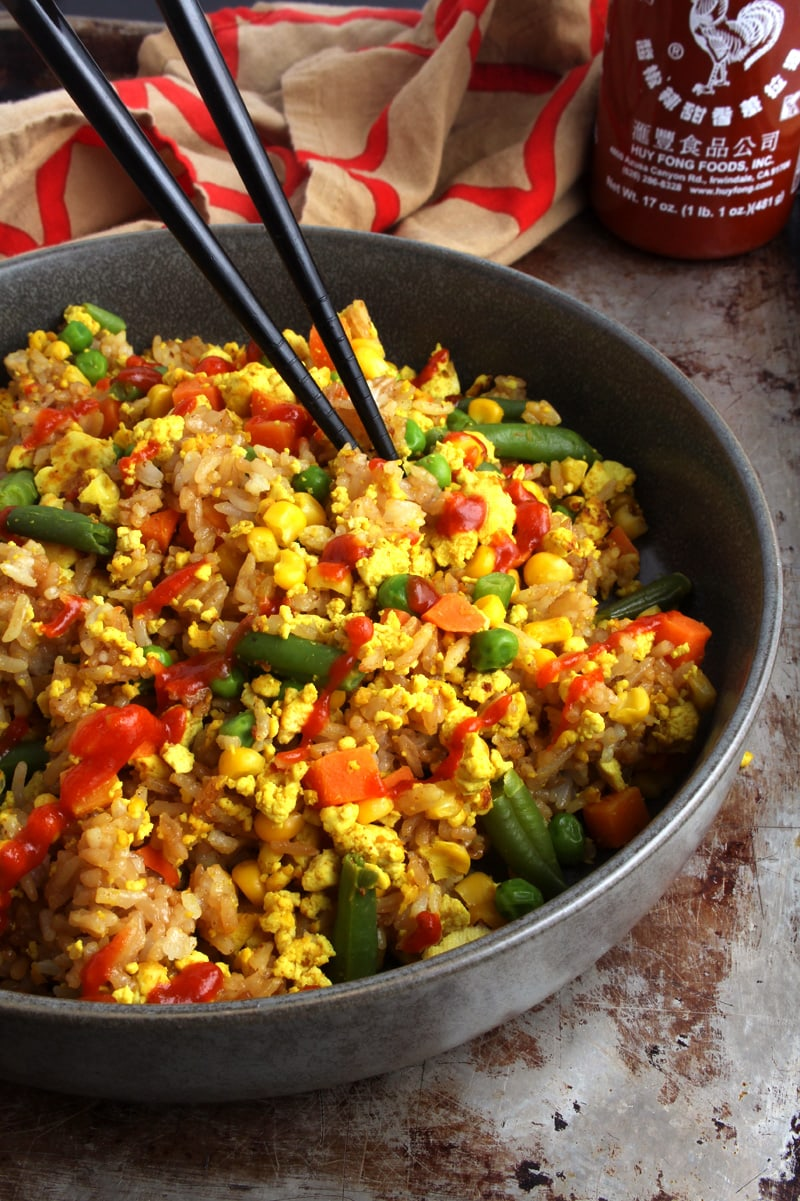 Picture of vegan fried rice with chopsticks and Sriracha sauce.