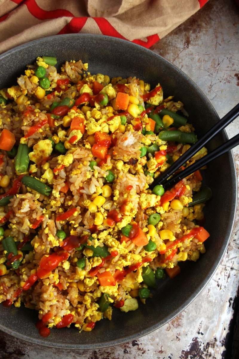 Picture of chopsticks in a bowl of vegan fried rice.
