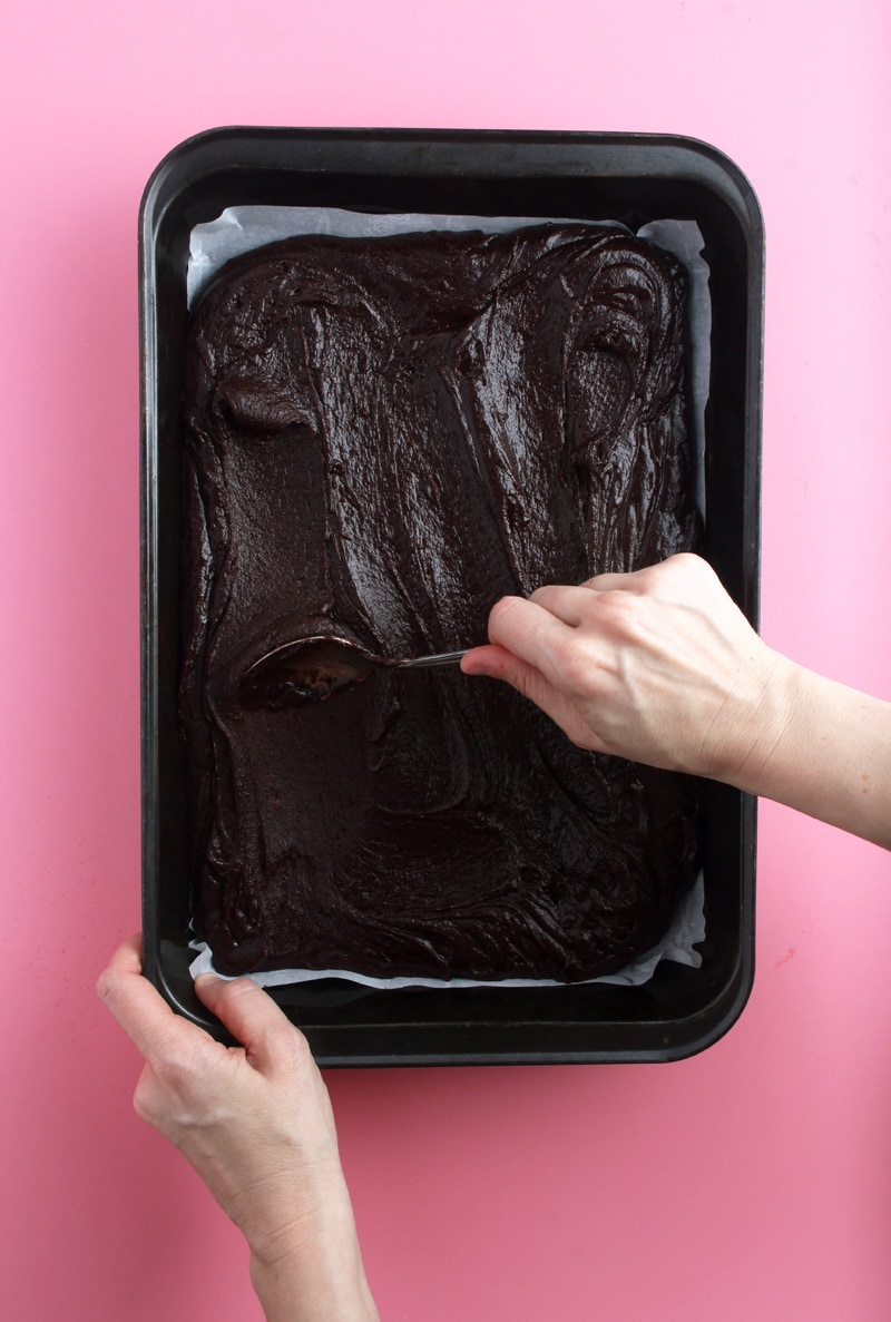 picture of hands spreading out brownies batter with a spoon.