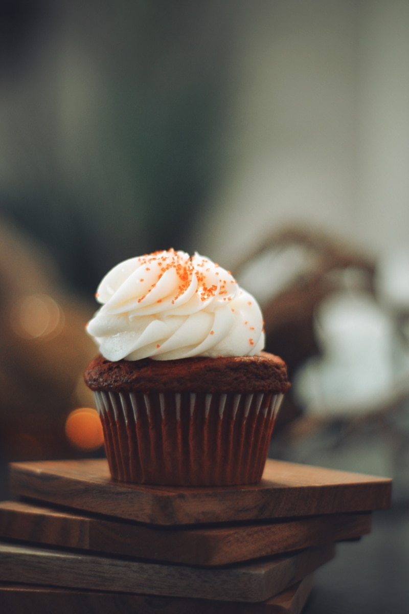 substitute eggs in baking: image of a chocolate cupcake with vanilla icing on blocks of wood.