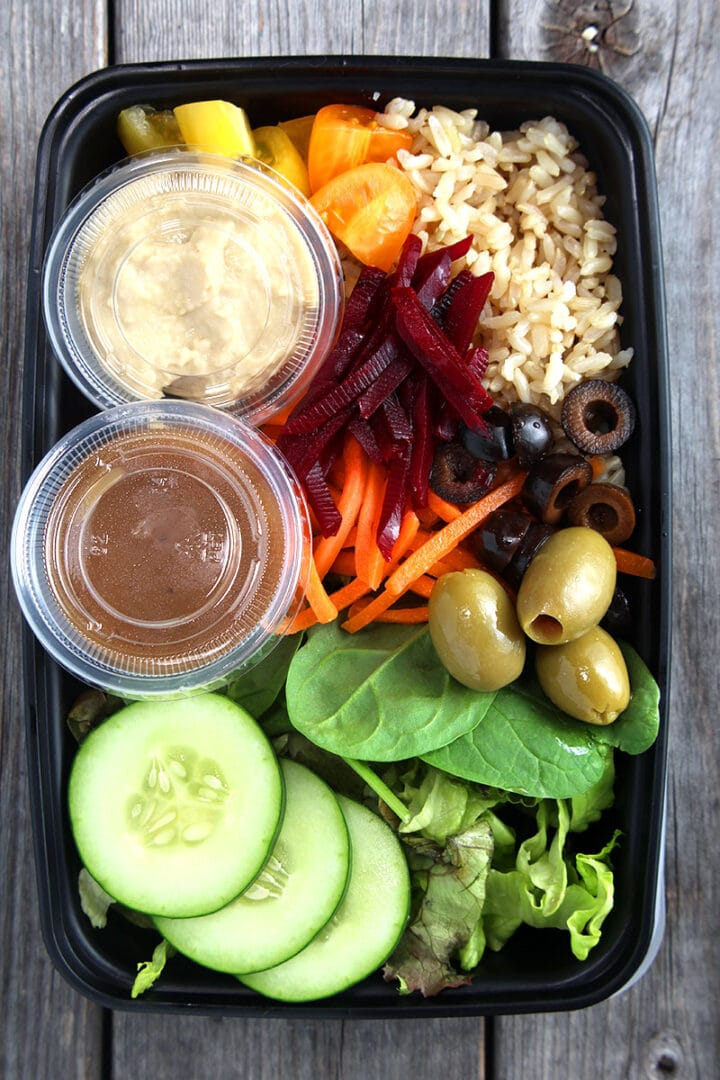 The Greek bowl being shown in a lunch to-go container, with two cups (one for dressing and one for hummus).