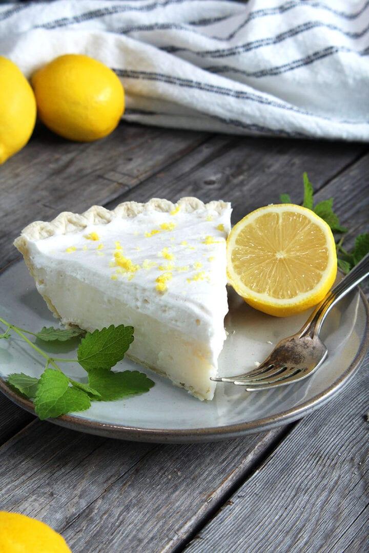 vegan lemon pie sliced with a wedge of lemon