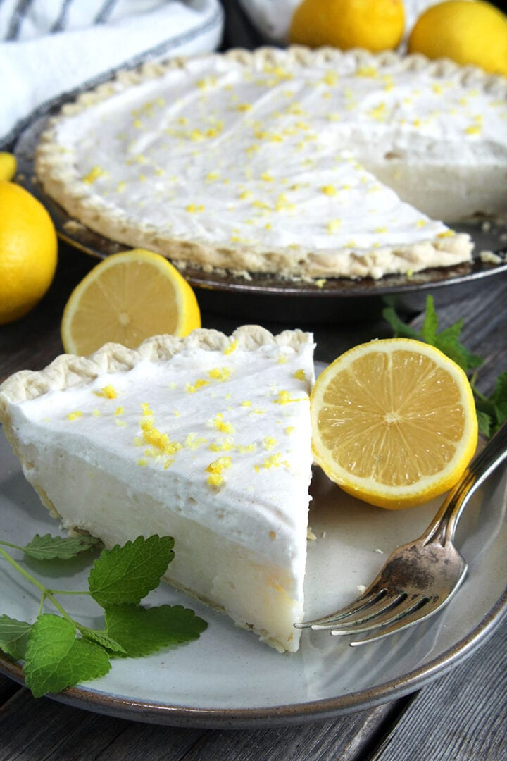beautiful picture of a fresh slice of vegan lemon pie on a plate with a fork