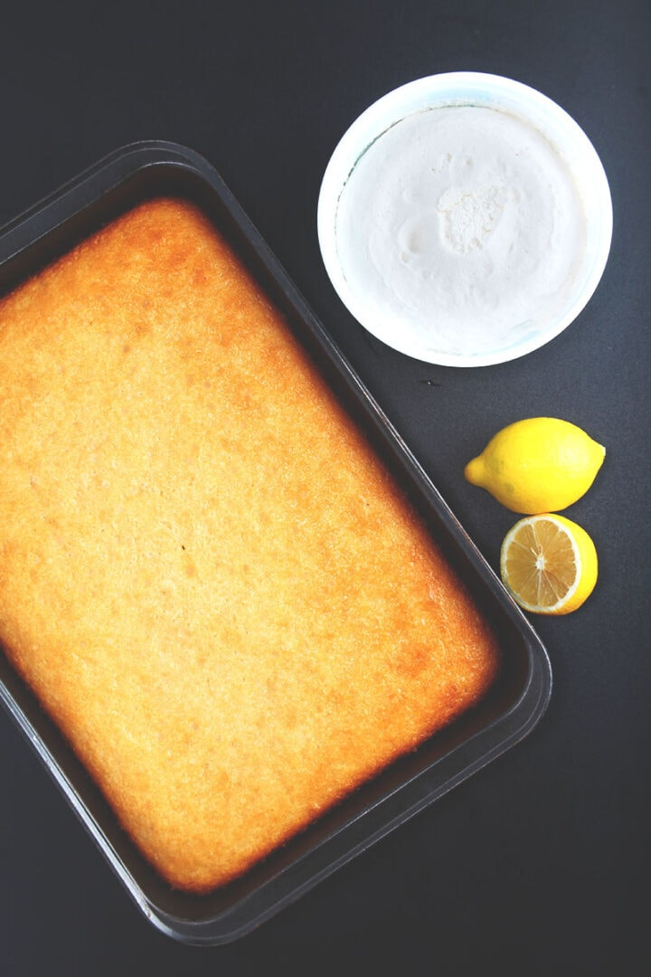 finished vegan lemon cake out of the oven, ready to be topped with coconut