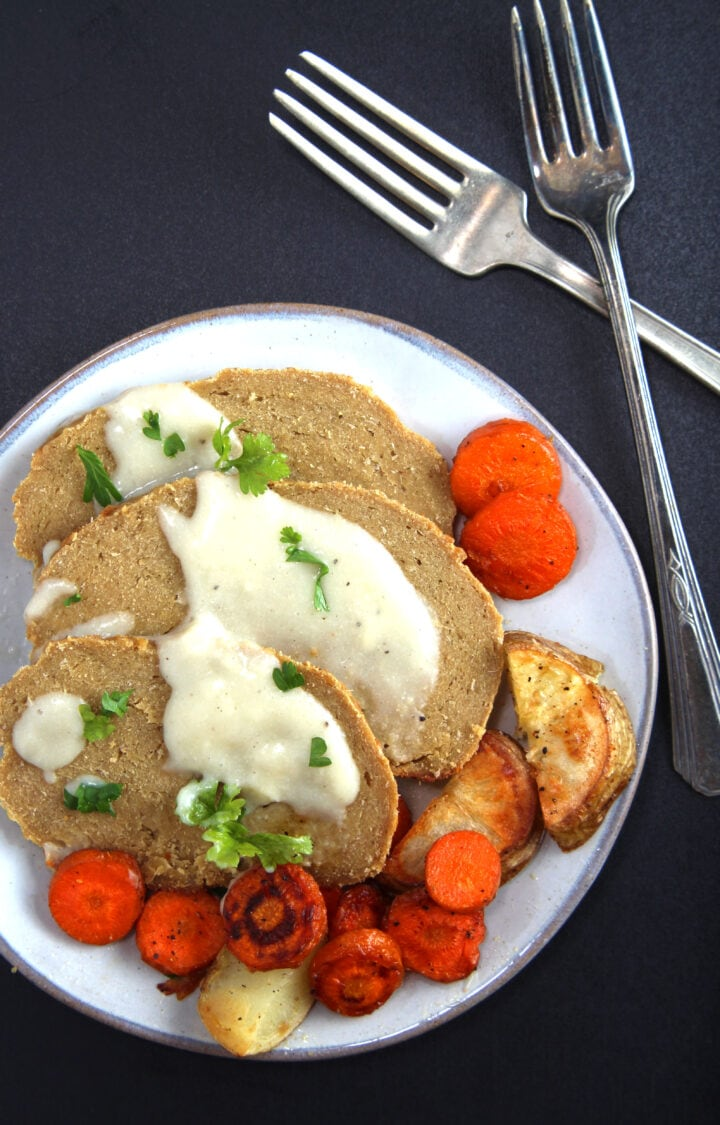picture of a plate of vegan turkey with gravy and vegetables