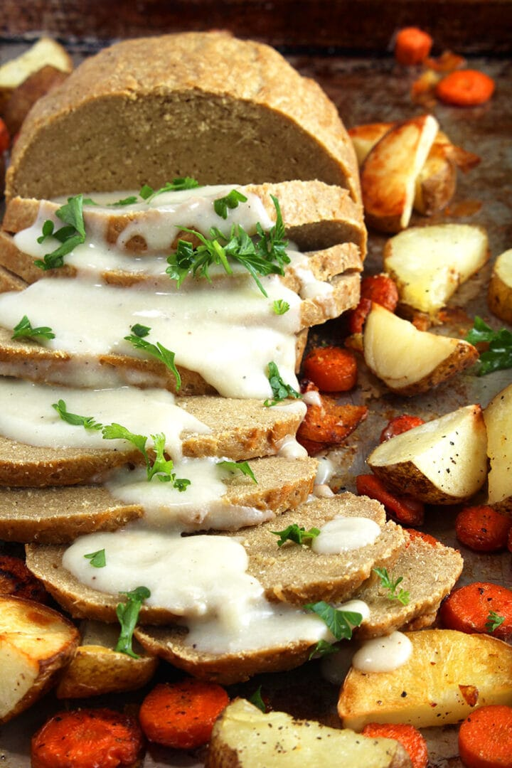 picture of vegan turkey sliced with gravy and parsley on top