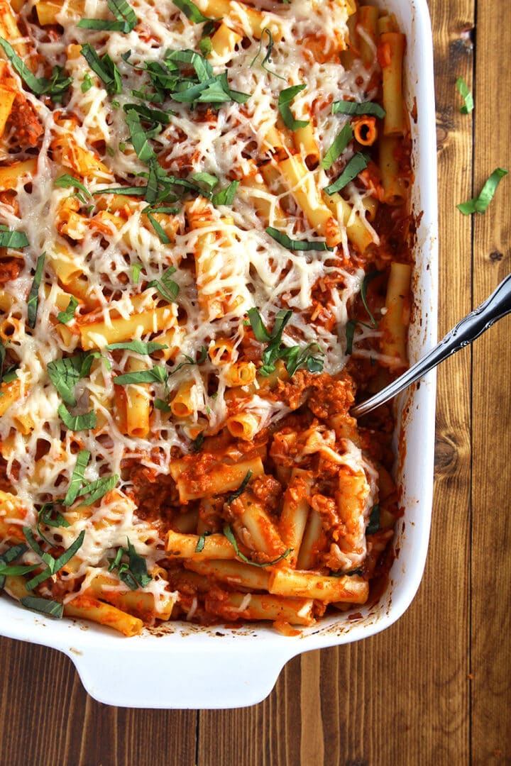 overhead picture of vegan baked ziti casserole with spoon in dish