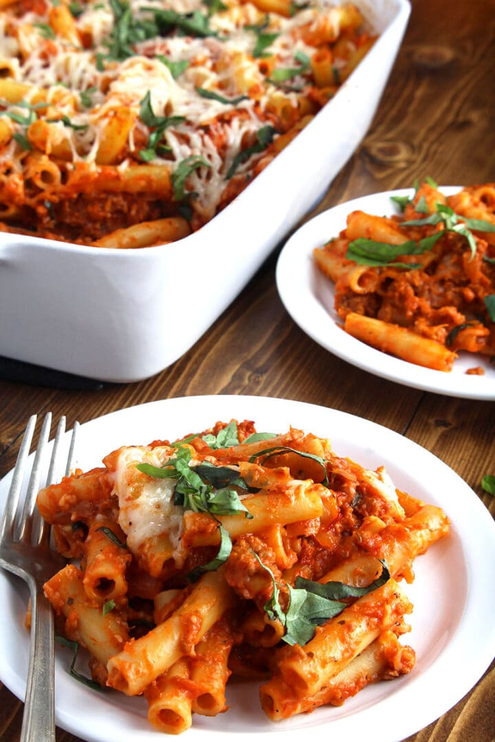 picture of two plates of vegan baked ziti beside the casserole dish