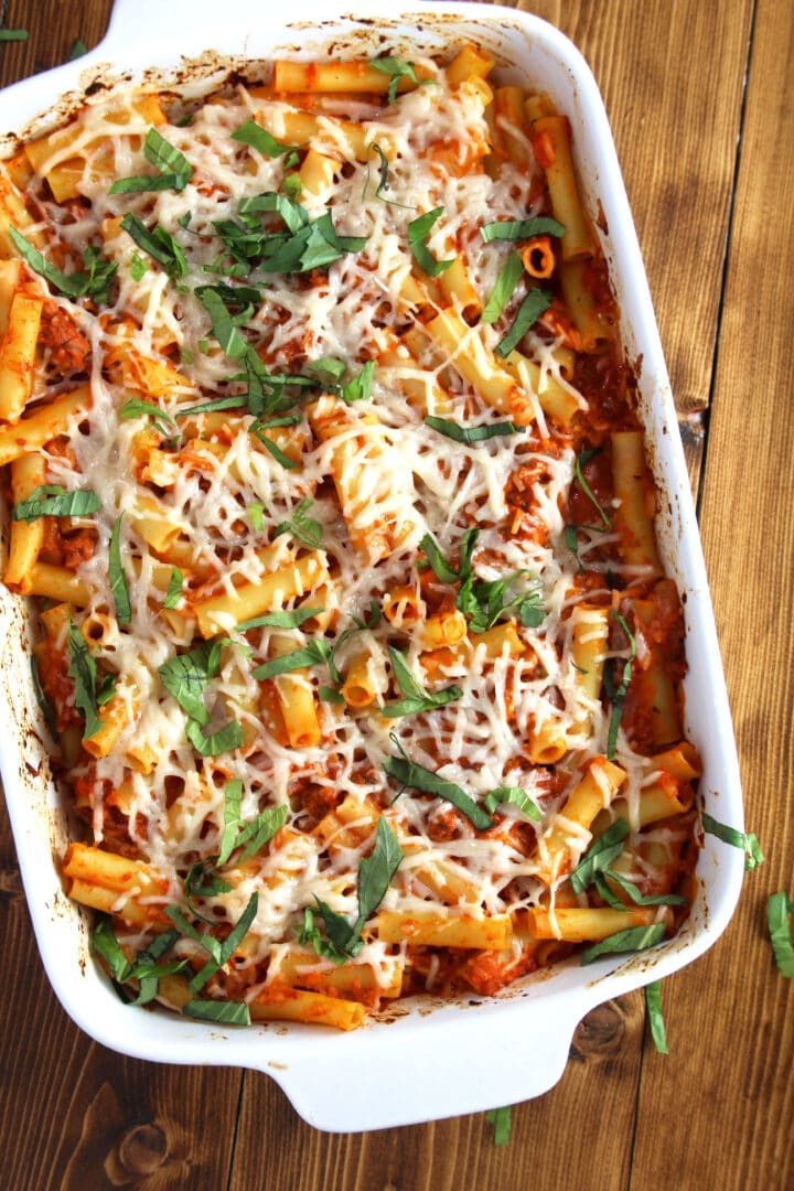 picture of vegan baked ziti in casserole dish with fresh basil, ready to eat